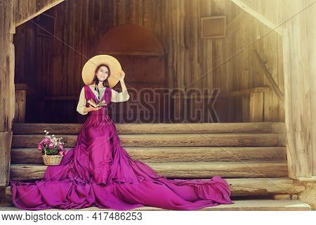 Romantic Woman In Summer Hat Long Pink Dress Reading Book Sitting On Steps Outside House. Rustic 19t