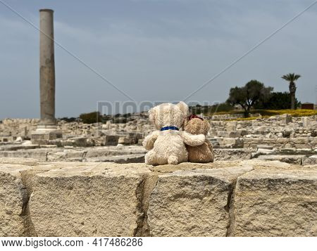 Two Small Teddy Bears Sitting On Stone Wall At Ancient Archaeological Site