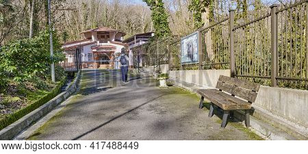Sochi, Russia - February 27, 2020: Man With Backpack Walks Along Road To Entrance To Yew-boxwood Gro