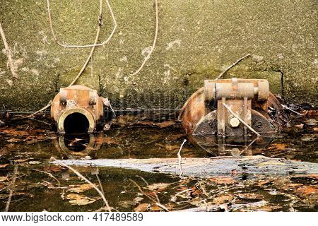 Water Inlet And Outlet Half Submerged In Dirty Canal Of A 19th Century Factory.