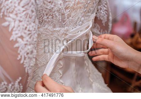 Back View Of Wedding Dress, Bridesmaid Hands Tying Bride Dress