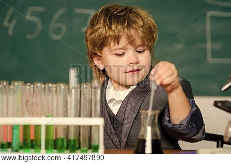 School Kid Scientist Studying Science. Science Experiments With Microscope In Lab. Little Boy Is Mak