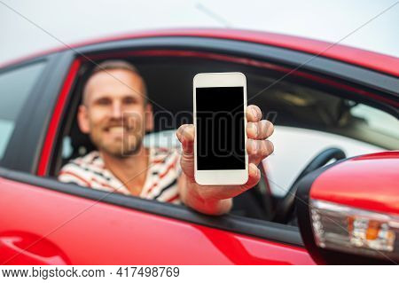 A Man In A Car Holds A Smartphone In His Hands. The Driver Shows A Smartphone With A Blank Screen.