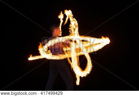 Energetic Man Performer Create Sparkling Fire Patterns Twirling Burning Baton In Dark Outdoors, Pyro