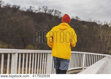 Active Man Jogging On The Bridge Pathway As Part Of Daily Morning Workout Routine