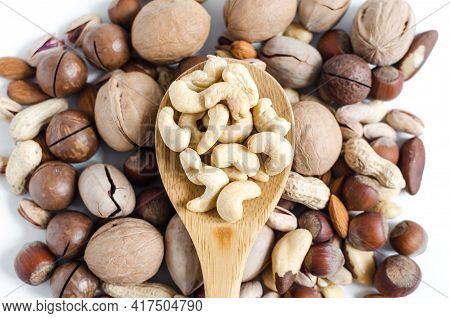 Cashew Nuts In A Wooden Spoon On The Background Of A Scattering Of Different Nuts Assorted Nuts