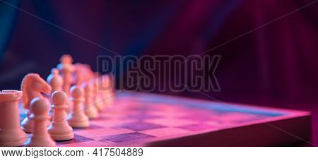 Chess Pieces On A Chessboard On A Dark Background Shot In Neon Pink-blue Colors. The Figure Of A Che