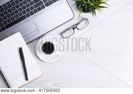 Top View Of Office Work Space, Wooden Desk Table With Laptop Notebook,keyboard ,pen,eyeglasses,phone