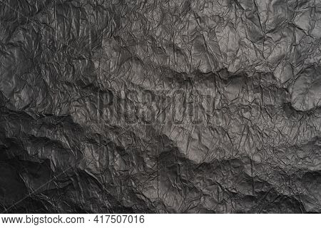 Black Crumpled Paper Texture In Low Light Background. Black Matte Crumpled Paper Background, Abstrac