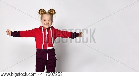 Little Blonde Curly-haired Beautiful Girl In A Red Burgundy Tracksuit Stands With Her Arms Spread Wi