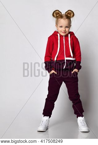 Little Blonde Curly-haired Beautiful Girl In A Red Burgundy Tracksuit And White Sneakers Stands With