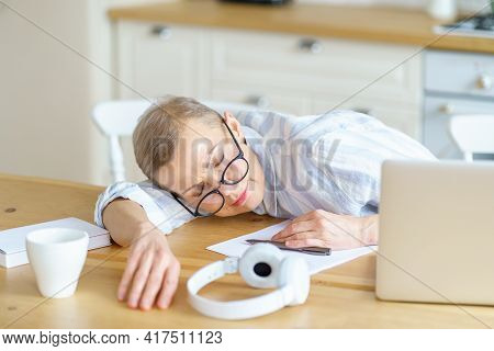 Middle Aged Tired Woman Wearing Glasses Sleeping On Wooden Table In Kitchen While Working Or Studyin