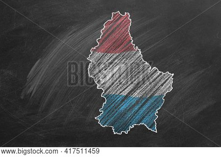 Country Map And Flag Of Luxembourg Drawing With Chalk On A Blackboard. One Of A Large Series Of Maps