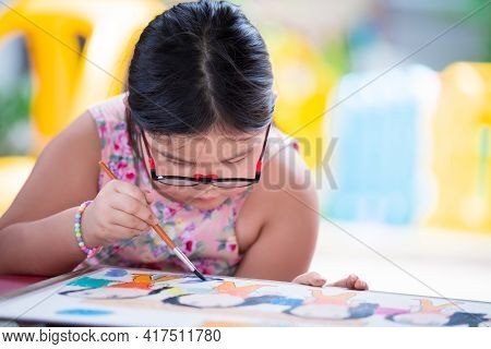Asian Girl Is Doing Art Paint On White Paper. Child Wear Glasses. Cute Children Make Crafts. Kid Stu