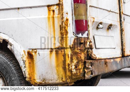 Rust On The Rear Wing Of A White Minibus, Old Rusty Car. Depreciation Of A Automobile Or Road Vehicl