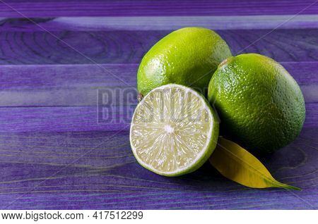 Green Limes And Half A Lime On A Colored Wooden Background Of Kopi Space