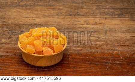 dried mango fruit diced - a small wooden bowl against rustic weathered wood