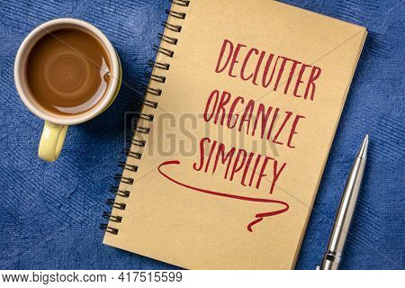 Declutter, organize, simplify. Motivational handwriting in a spiral notebook with a cup of coffee. Business, productivity, lifestyle and personal development concept.