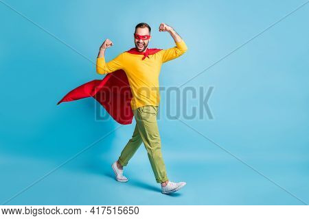 Full Size Photo Of Young Handsome Powerful Superhero Go Walk Showing Muscles Biceps Isolated On Blue