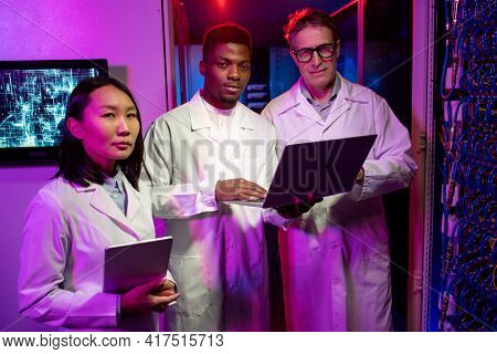 Portrait of confident multi-ethnic network scientists in lab coats standing with devices in neon-illuminated server room