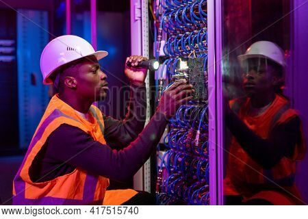 Concentrated Black workman in hardhat and orange vest crouching by server and using flashlight while fixing server problem