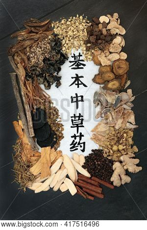 Chinese fundamental herb collection regularly used in herbal medicine with calligraphy script on rice paper. on black wood.  Translation reads as Chinese fundamental herbs. Top view.
