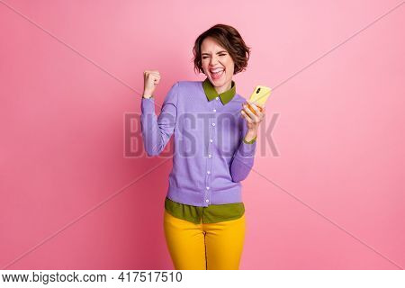 Photo Of Excited Lady Hold Telephone Win Free Device Wear Purple Jumper Yellow Pants Isolated Pink C