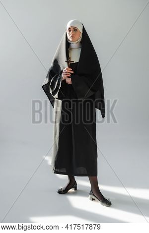 Full Length View Of Young Nun In Black Vestment Standing With Crucifix On Grey Background.