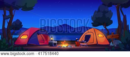 Camping Tents On River Bank, Mountains And Night Sky On Background, Bonfire And Lantern Lamp On Port