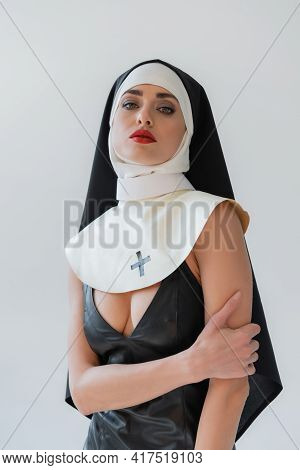 Seductive Nun In Leather Dress Looking At Camera While Posing Isolated On Grey.
