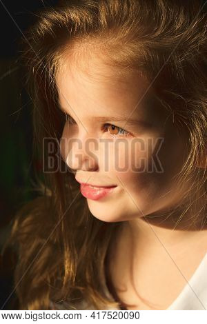 Portrait Of Happy Smiling Child Girl Daydreaming And Looking Out The Window. Shaft Of Light On Face.