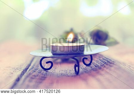 Blurred Glowing Small Candle. Retro Toned. Cozy Still Life. Concept Of Coziness