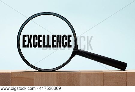 Cubes On A Light Blue Wooden Background. On Them A Magnifying Glass With The Word Excellence