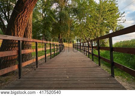 Wooden Bridge In The Park. Landscape In The Early Morning On A Spring Sunny Day