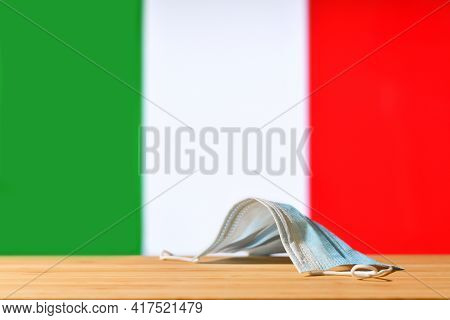 A Medical Mask Lies On The Table Against The Background Of The Flag Of Italy. The Concept Of A Manda