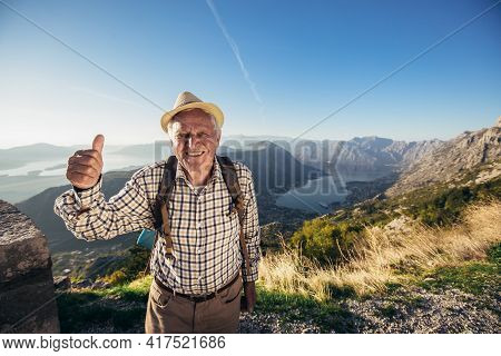 Happy Old Man Just Reaches The Top Of Hill.handsome Senior Man Hiking, Exploring.