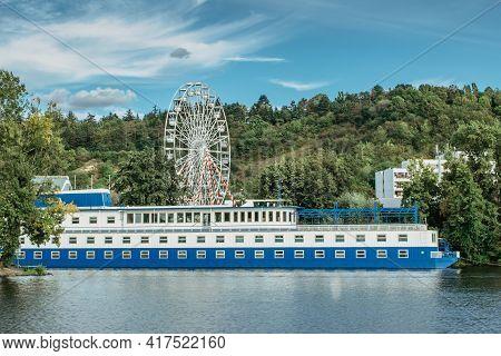 Large Tourist Boat With Restaurant Anchoring On Vltava River, Ferris Wheel In Background, Prague, Cz