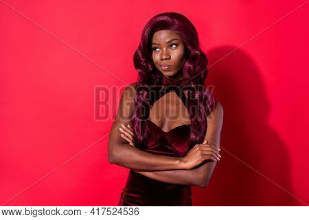 Photo Of Doubtful Young Dark Skin Woman Look Empty Space Hesitate Hold Arms Folded Isolated On Red C