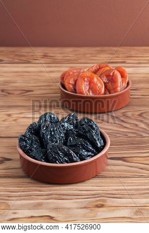 Dried Prunes And Dried Apricots Lying In Ceramic Bowls On A Wooden Table. Closeup. Macro