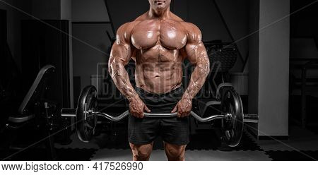 Powerful Bodybuilder Trains In A Gym With A Barbell. No Name Portrait. Bodybuilding Concept. Mixed M