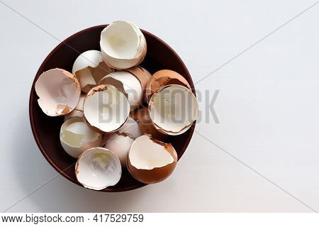Broken Egg Shell In A Bowl On White Background. Top View. Egg Shell Texture. Organic Ingredient For