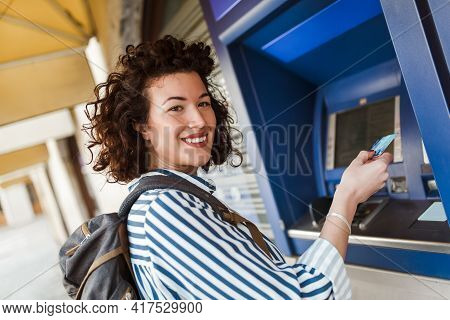 Attractive Tourist Woman Uses A Credit Card Near The Atm. The Concept Of Tourism, Travel, Leisure.