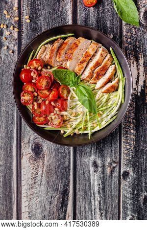 Fried Chicken Fillet And Fresh Vegetable Salad Of Tomatoes, Zucchini And Pine Nuts.