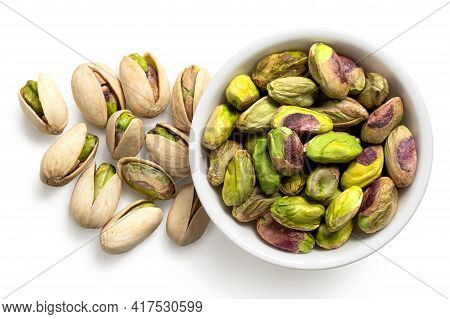 Shelled Pistachios In A White Ceramic Bowl Next To Pistachios In Shell Isolated On White. Top View.