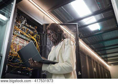 Low Angle Portrait Of African-american Female Network Engineer Standing By Server Cabinet And Holdin