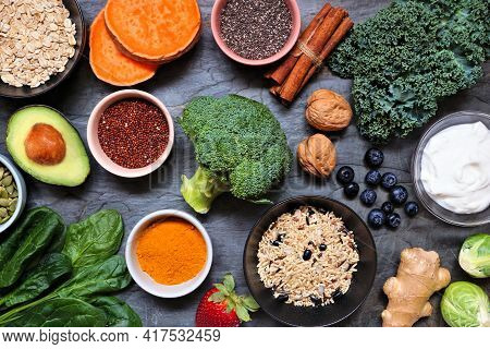 Group Of Healthy Food Ingredients. Top View Table Scene On A Dark Slate Background. Super Food Conce