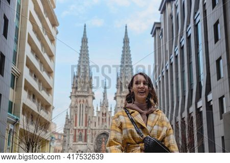 Happy Millenial Woman In A Yellow Coat In European City Near A Business Center And Historic Building
