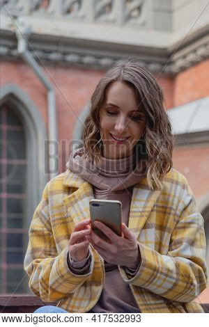 Happy Millenial Woman In A Yellow Coat In European City Near Historic Building.