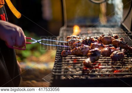 Human Hand Turns Chicken Drumsticks On A Barbecue Grill With Grilling Tongs. Cooking Food On An Open