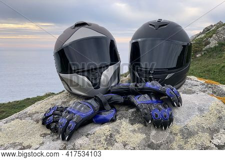 Close-up Of Two Motorcycle Helmets With Tinted Glasses And Leather Motorcycle Gloves On A Rock Again